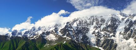 Panorama of Caucasian mountains of Svaneti. Panorama of high caucasian ridge covered with glaciers and clouds Royalty Free Stock Photos