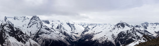 Panorama of the Caucasus mountains. The Dombai mountain landscape. Snowy peaks against the cloudy sky Stock Photos