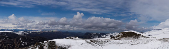 Panorama of the Caucasus mountains. The Dombai mountain landscape. Snowy peaks against the cloudy sky. Beautiful panorama of mountains. Panorama of the Royalty Free Stock Photography