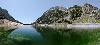 Panorama of Cavallers Lake in Catalan Pyrenees. Panorama of Estany de Cavallers Lake with Crystalline transparent water seen in the dam and  Boi valley direction Royalty Free Stock Images