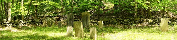 Panorama of cemetery headstones and green woods stock photos