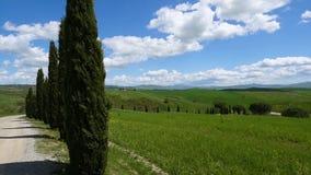 Panorama Chianti wzgórza z cyprysami, chmurami i drogą gruntową, Siena zbiory