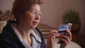 Panorama from Christmas gifts to woman using smartphone to shopping online with credit card. Online banking. Woman in glasses using smartphone to shopping stock video footage