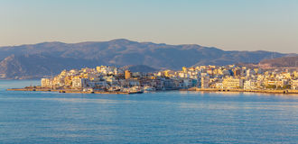 Panorama of the city, illuminated by the yellow light of the rising sun, Agios Nikolaos royalty free stock images