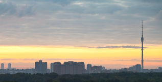 Panorama of city under grey clouds at sunrise Royalty Free Stock Images