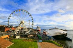 Panorama of ciy, pier, cruise ships in sea port Helsinki and ferris wheel. Helsinki, Finland - November 4, 2017: Scenic panorama of old town, embankment and big Royalty Free Stock Images