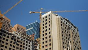 Panorama from clear blue sky to buildings under construction with cranes in summer day. Panorama from clear blue sky to buildings under construction with cranes stock footage