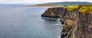 Panorama of Cliffs of Moher with Doolin village and farm fields. In background, Clare, Ireland royalty free stock image