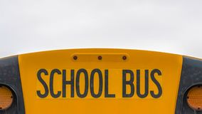 Panorama Close up of the back side of a yellow school bus against homes and cloudy sky. The rear glass window of the bus also serves as an emergency exit for stock photography