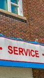 Panorama Close up of building exterior with a huge sign that reads Sales Service Parts. The old building has brick wall and the windows have white frames royalty free stock photos