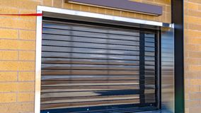 Panorama Close up of a building with glossy industrial roller shutter on the window royalty free stock photography