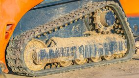 Panorama Close up of the dirty rubber track of a heavy duty construction machinery stock photo