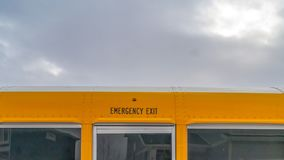 Panorama CLose up of the exterior of a yellow school bus against cloudy sky. One of the windows serves as an exit for the passengers in case of an emergency royalty free stock photography