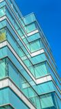 Panorama Close up of an office building exterior against blue sky on a sunny day. Roller blinds on the windows provide shade and privacy to the rooms stock photo