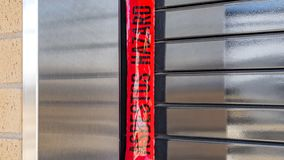 Panorama Close up of the window of a building with security roller shutter. A red danger and hazard tape is tied at the corner of the window royalty free stock photo