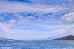Clouds Lace in Blue Sky above Azure Sea Hill Distant City Royalty Free Stock Photography