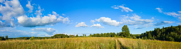 Panorama of clouds and meadow Stock Images