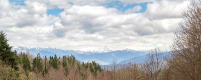 Panorama of the cloudy sky, forests and mountains in the Caucasus Stock Photography