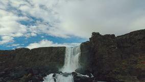 Panorama from cloudy sky to waterfall Oxararfoss on basalt rocks in Iceland in autumn day. Panorama from cloudy sky to small amazing waterfall Oxararfoss on stock video footage