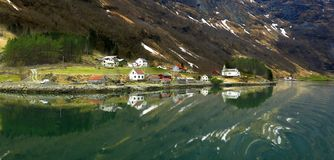 Panorama of colorful Scandinavian houses reflected in Norwegian fjord. Panorama of colorful clapboard Scandinavian houses reflected in tranquil water of Royalty Free Stock Photo