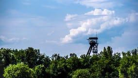 Panorama com um eixo de mina em um fundo do céu azul Imagem de Stock