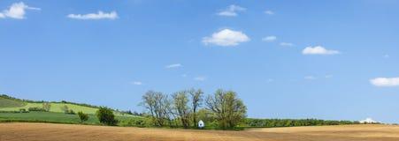 Panorama con cielo blu ed il boschetto con poca cappella Immagine Stock