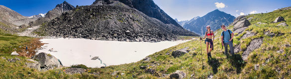 Panorama con due turisti nelle montagne nei precedenti di Immagini Stock Libere da Diritti