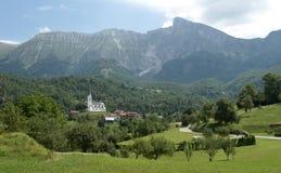 Panorama con el pueblo Drezniske Ravne debajo de la montaña de Krn en Julian Alps en Eslovenia Fotografía de archivo