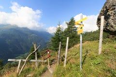 Panorama con el sendero, los postes indicadores y las montañas en las montañas de Hohe Tauern, Austria Foto de archivo libre de regalías