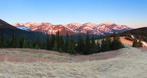 Panorama con las montañas El top de las colinas cubiertas con nieve El césped con la hierba secada Salida del sol mágica del bosq Imagen de archivo libre de regalías