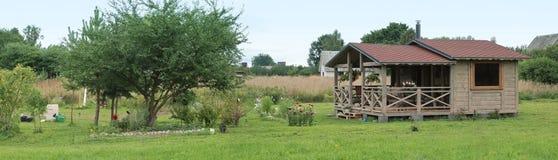 Panorama con una pequeña casa de campo del verano y un jardín Foto de archivo libre de regalías