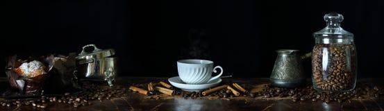 Panorama con una taza de café, de granos de café y de molletes Fotos de archivo libres de regalías