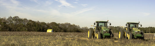 Panorama of cotton field with two tractors. Prattville, Alabama, USA - November 5, 2016: Panoramic view of a cotton field after harvest with a wrapped bale of Royalty Free Stock Photo