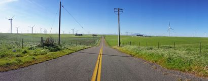 Panorama of a country road with wind turbines on either side. The double yellow line going down this road is of no consequence since it`s as empty as the fields Stock Photo