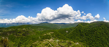 Panorama of the countryside in Abkhazia. Panorama of the countryside with meadows, roads, houses and mountains with blue sky and clouds in Abkhazia royalty free stock photography