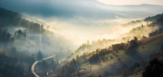 Panorama of countryside in glowing fog. Panorama of amazing scenery in mountains at sunrise. glowing fog rise from forest on hills and fall in to the valley. ray stock image