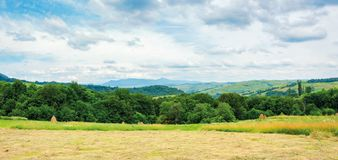 Panorama of a countryside in mountain on a cloudy day. Beautiful landscape with rural hay fields on hills near the forest. ridge with high peak in the distance stock photo