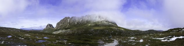 A panorama of a Cradle Mountain and Tasmania`s Overland Track. With fog over the summit and a hiker on the trail with some snow and water on the ground stock images