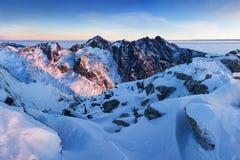 Panorama d'altezza della catena montuosa di Tatras di inverno con molti picchi e chiaro cielo Giorno soleggiato sopra le montagne fotografia stock libera da diritti
