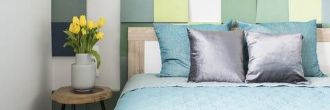 Panorama d'intérieur coloré de chambre à coucher avec les tulipes jaunes sur le bois photos libres de droits