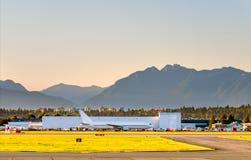 Panorama d'un aéroport et des avions blancs dans la perspective d'un ciel orange et bleu de soirée Photo stock