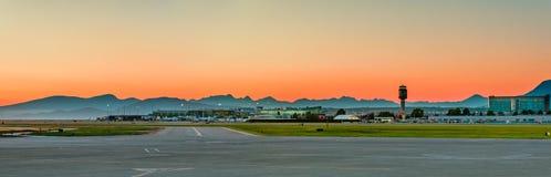 Panorama d'un aéroport moderne et des avions blancs dans la perspective d'une soirée orange Photo stock