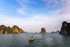 Panorama da baía de Halong com o barco de pesca tradicional no por do sol, herança natural do mundo do UNESCO, Vietname imagem de stock royalty free