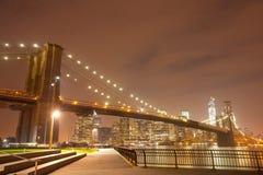 Panorama da noite de New York City com ponte de Brooklyn foto de stock