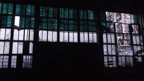 Panorama da parede da construção abandonada velha com janelas quebradas dentro de um hangar escuro no dia filme