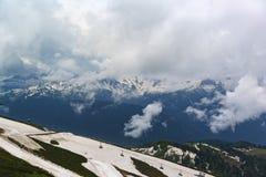 Panorama dalle vette nevose nelle nuvole e nel pendio di collina, forniti di cabine di funivia nella priorità alta Immagini Stock Libere da Diritti