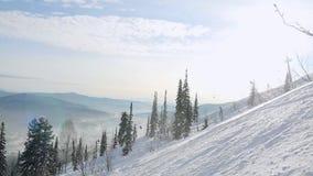 Panorama das montanhas do inverno com inclinações do esqui através do sol em Sheregesh no movimento lento com efeitos do alargame vídeos de arquivo