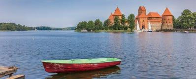 Panorama de château de Trakai et d'un bateau rouge et vert dans le lac Galve Photographie stock