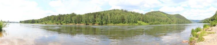 Panorama de colinas boscosas a través del río Fotografía de archivo libre de regalías