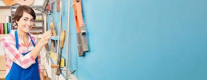 Panorama de femme à côté des outils à l'atelier Image libre de droits